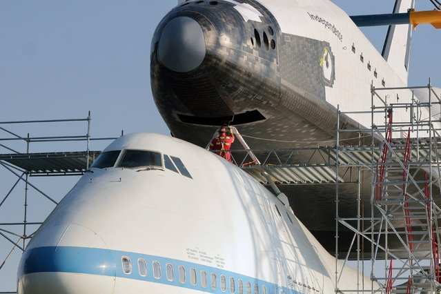 A worker lines up the mount as a space shuttle replica is lifted into place atop the Shuttle Carrier Aircraft (SCA) Thursday morning, August 14, 2014, at NASA's Johnson Space Center  in Houston. The old Boeing 747 formerly transported shuttles piggyback to Florida following flights. Visitors will be allowed to enter both vehicles when the permanent exhibit opens in 2015. (Photo by Kar B. Hlava/AP Photo/Conroe Courier)