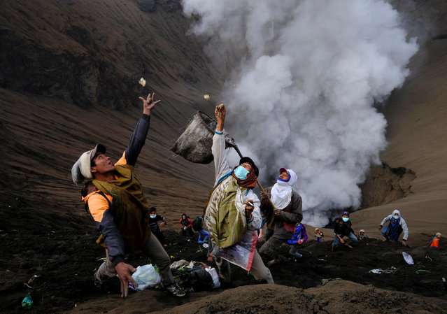 Villagers standing on the slopes near the crater of Mount Bromo try to catch money thrown in by worshippers as smoke and ash rise from the volcano, during Kasada ceremony, when villagers and worshippers throw offerings, livestock and other crops into the volcanic crater of Mount Bromo, in Probolinggo, Indonesia, July 21, 2016. (Photo by Reuters/Beawiharta)