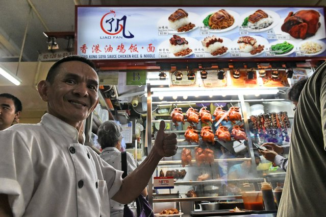 Singaporean chef Chan Hon Meng (front L) poses infront of his Hong Kong Soya Sauce Chicken Rice and Noodle stall in Singapore on July 22, 2016. Culinary bible Michelin on July 21 awarded one star each to two street food hawkers in Singapore, the first in the guide's history. Launching the inaugural restaurant and hotel guide to the Southeast Asian city-state, Michelin inspectors gave one star each to Hill Street Tai Hwa Pork Noodle and Hong Kong Soya Sauce Chicken Rice & Noodle. (Photo by Roslan Rahman/AFP Photo)