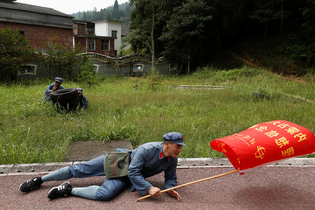 "A man in ""Red Army"" garb hits the pavement during a simulated attack during a re-staging of part of the Long March in Jinggangshan September 14, 2017. The scene brings alive an extraordinary chapter in China's history that established the supremacy of Chairman Mao Zedong and the Communist Party. Deep in the mountains of Jinggangshan in the southeastern province of Jiangxi, a classroom of bank tellers participates in an ideological boot camp that plays into Chinese President Xi Jinping's drive to further consolidate his grip on power. (Photo by Thomas Peter/Reuters)"