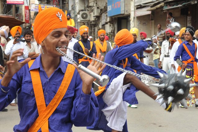 "An Indian Nihang, a religious Sikh warrior, shows his skill in the Sikh martial art known as ""Gatka"" during a march to mark the 353th birth anniversary of the Sikh warrior Shaheed Baba Jiwan Singh at the Golden temple in Amritsar on September 3, 2014. The Sikhs celebrate Shaheed Baba Jiwan Singh who was a famous warrior from the Sikh religion during the 17th century. (Photo by Narinder Nanu/AFP Photo)"