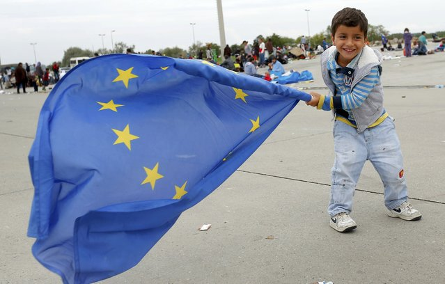 A young migrant child plays with a European Union flag after crossing the Austrian border in Nickelsdorf September 5, 2015. (Photo by Laszlo Balogh/Reuters)