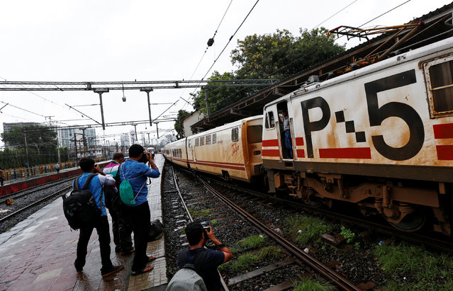 News photographers take pictures of high speed Talgo train as it arrives at a railway station during its trial run in Mumbai, India August 2, 2016. The train consists of nine coaches, two executive class, four chair cars, a cafeteria, a power car and a tail-end coach for staff and equipment. The Talgo train runs at an average speed of around 90-100 km/hr and can attain a maximum speed of 130-150 km/hr. (Photo by Danish Ismail/Reuters)