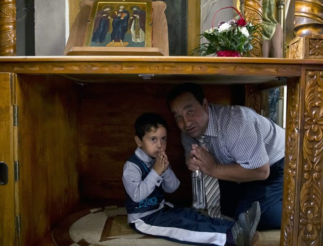 A Romanian Roma man teaches his son to pray during a religious service celebrating the Birth of the Virgin Mary at the Bistrita Monastery in Costesti, Romania, Monday, September 8, 2014. (Photo by Vadim Ghirda/AP Photo)