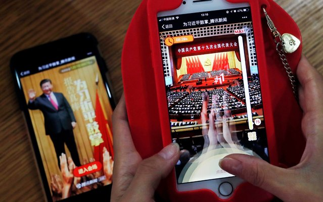 """A woman poses as she playing a Tencent's smartphone game called """"A Great Speech, clap for Xi Jinping"""" in Beijing, Friday, October 20, 2017. Ordinary young Chinese may not have paid close attention to Xi Jinping's 3-and-a-half hour marathon speech this week, but they're happy to """"applaud"""" the president in the newest viral phenomenon to sweep China's internet. (Photo by Andy Wong/AP Photo)"""