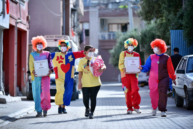 Volunteer clowns distribute clothes and toys to children for the upcoming Eid al-Fitr festival alongside complying coronavirus (Covid-19) pandemic restrictions in Mersin, Turkey on May 21, 2020. Due to the pandemic a group of the clowns take a break from their daily performances to do welfare activities for people in need in Ramadan. (Photo by Serkan Avci/Anadolu Agency via Getty Images)