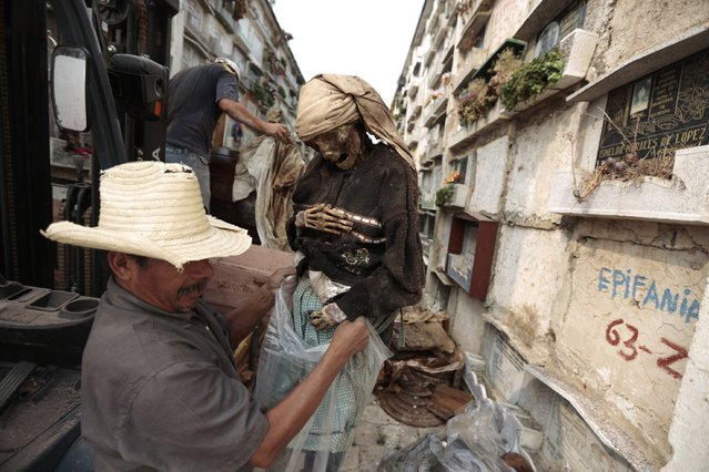 A grave cleaner holds the mummified body of a woman during exhumation works at the Verbena cemetery in Guatemala City April 17, 2013. Bodies that have been stored in the upper crypt are exposed to dry and sunny conditions which means they do not decompose and instead become mummified. (Photo by Jorge Dan Lopez/Reuters)