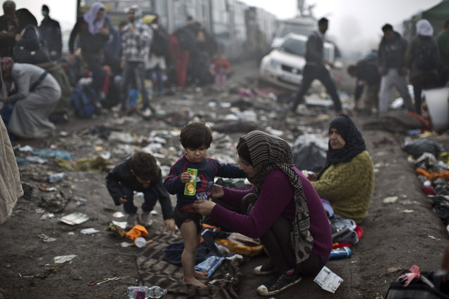 A Syrian woman changes her son's clothes near a makeshift camp for asylum seekers, after crossing the Serbian-Hungarian border near Roszke, southern Hungary, Saturday, September 12, 2015. Hundreds of thousands of Syrian refugees and others are still making their way slowly across Europe, seeking shelter where they can, taking a bus or a train where one is available, walking where it isn't. (Photo by Muhammed Muheisen/AP Photo)
