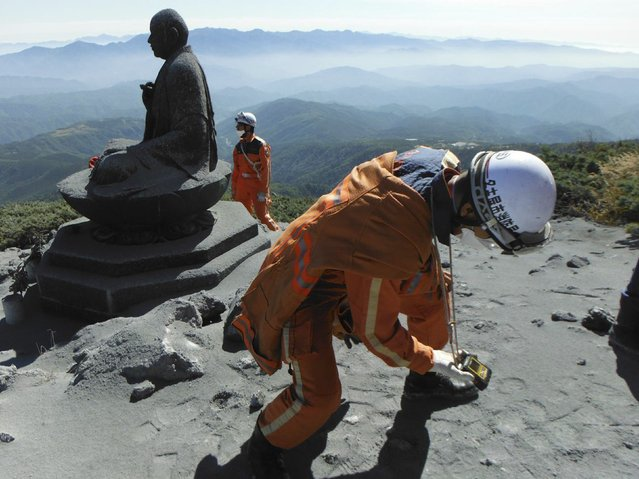 A firefighter checks toxic gas levels during rescue operations near the peak of Mt. Ontake, which straddles Nagano and Gifu prefectures, central Japan, in this handout photograph released by Nagoya City Fire Bureau and taken September 28, 2014. Search and recovery efforts for at least two dozen victims of Japan's worst volcanic eruption in decades were called off on Tuesday due to worries about rising volcanic activity, including the chance of another steam explosion. (Photo by Reuters/Nagoya City Fire Bureau)