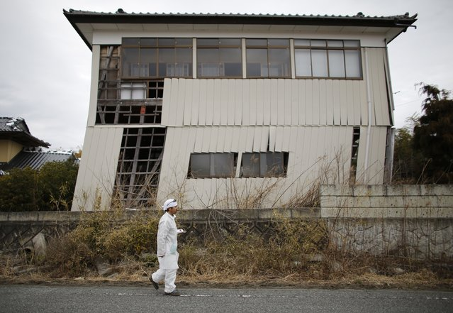 Norio Kimura, 49, who lost his father, wife and daughter in the March 11, 2011 tsunami, walks in front of a house, damaged by the March 11, 2011 earthquake inside the exclusion zone in Okuma town, next to Tokyo Electric Power Co's (TEPCO) tsunami-crippled Fukushima Daiichi nuclear power plant February 23, 2015. (Photo by Toru Hanai/Reuters)