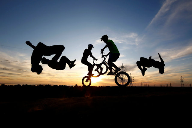 Iraqi youths wearing protective face masks use bicycles and perform a somersault as they practice parkour, following the outbreak of the coronavirus disease (COVID-19), during the holy month of Ramadan in the holy city of Najaf, Iraq on May 3, 2020. (Photo by Alaa al-Marjani/Reuters)