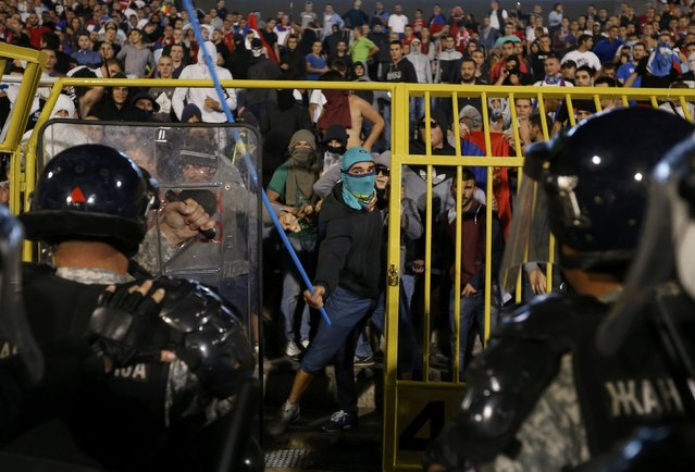 Fans of Serbia face the riot police during the Euro 2016 Group I qualifying soccer match between Serbia and Albania at the FK Partizan stadium in Belgrade October 14, 2014. (Photo by Marko Djurica/Reuters)
