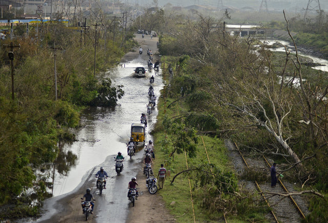 Vehicles move through a flooded road next to the trees fallen over railway tracks after being damaged by strong winds caused by the Cyclone Hudhud in Visakhapatnam October 14, 2014. (Photo by R. Narendra/Reuters)