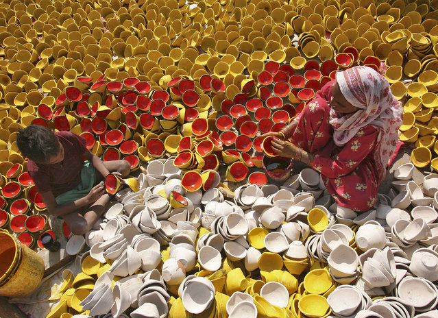 Potters colour earthen lamps at a workshop ahead of the Hindu festival of Diwali in Amritsar October 15, 2014. Earthen lamps are sold in large numbers during Diwali, the annual Hindu festival of lights, as people use them to decorate their homes. (Photo by Munish Sharma/Reuters)