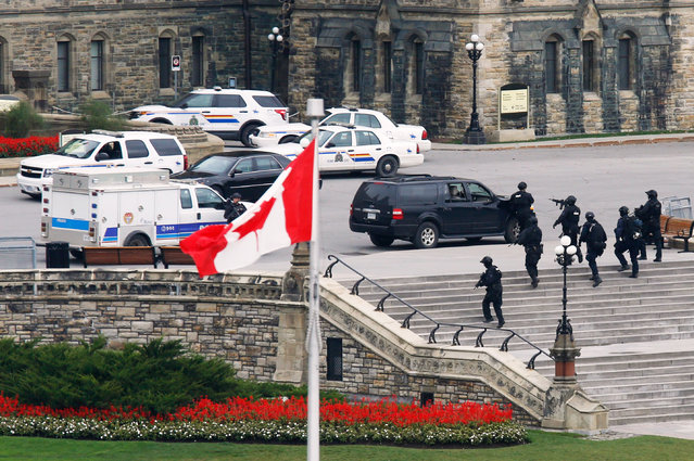 Armed RCMP officers approach Centre Block on Parliament Hill following a shooting incident in Ottawa October 22, 2014. (Photo by Chris Wattie/Reuters)