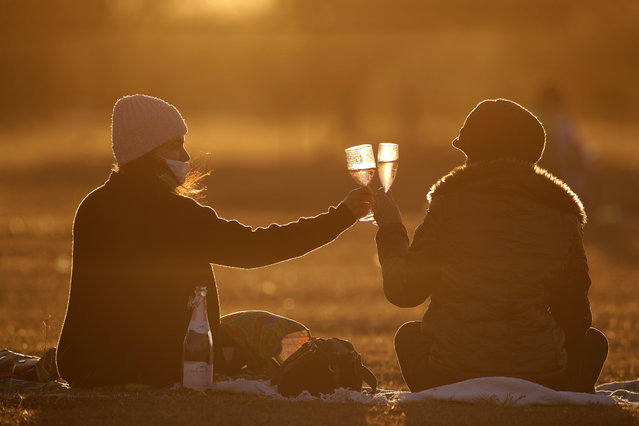 Women toast during a sunset at Cruzeiro Square in Brasilia, Brazil, Friday, July 31, 2020. People gathered in the late afternoon as authorities eased the restrictions related to the new coronavirus, despite that Brazil's official COVID-19 death toll is the second highest in the world after the United States. (Photo by Eraldo Peres/AP Photo)