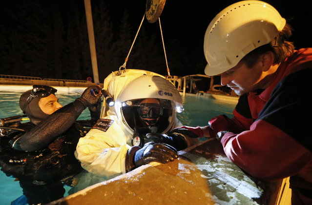 Comex Space division manager Peter Weiss (R) checks the Gandolfi space suit of National Diving School director Jerome Vincent (C) with Comex's astronaut-diver Julien Bonini (L) during a training session in a swimming pool in Marseille October 22, 2014. (Photo by Jean-Paul Pelissier/Reuters)