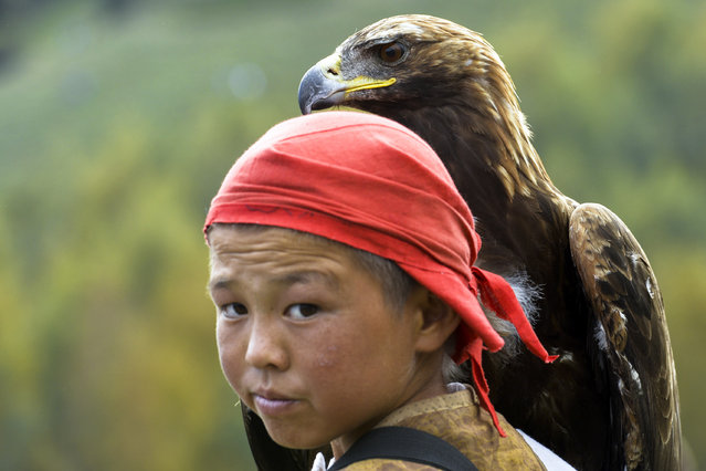 In this photo taken on Sunday, September 4, 2016, a Kyrgyz boy holds a golden eagle during the second World Nomad Games at Issyk Kul lake in Cholpon-Ata, Kyrgyzstan. (Photo by Vladimir Voronin/AP Photo)