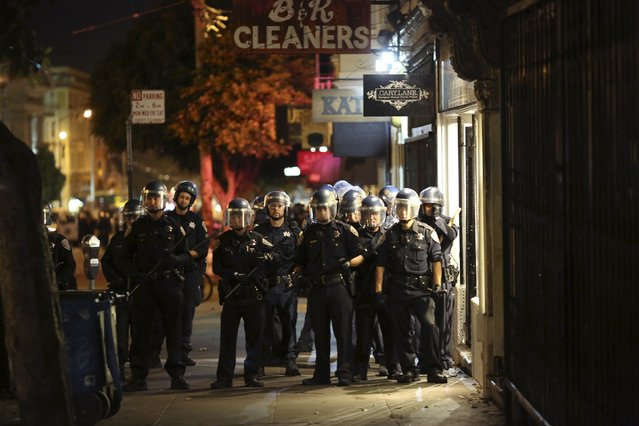 Police prepare to disperse a crowd gathered in the Mission District in San Francisco, California October 29, 2014. (Photo by Robert Galbraith/Reuters)