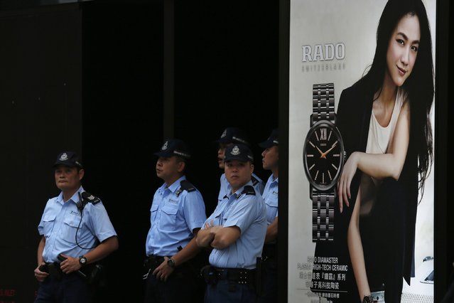 Police officers on patrol stand beside an advertisement at a road occupied by pro-democracy protesters at Mongkok shopping district in Hong Kong October 27, 2014. Hong Kong has been roiled by a tenacious, student-led people's movement demanding full democracy in the former British colony that returned to Chinese rule in 1997. (Photo by Bobby Yip/Reuters)