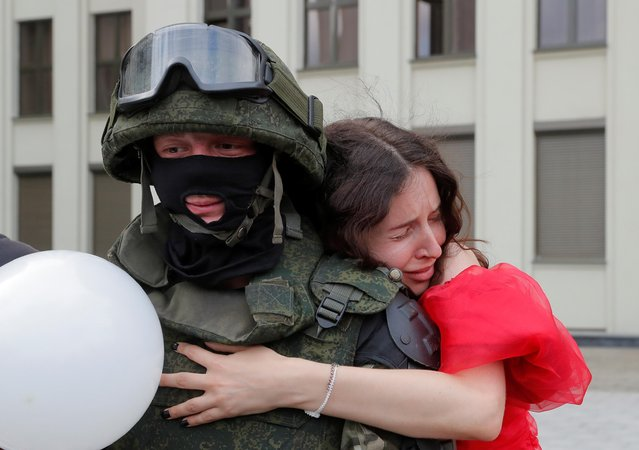 A participant embraces a member of Belarusian Interior Ministry troops, who stands guard during an opposition demonstration to protest against police violence and to reject the presidential election results near the Government House in Independence Square in Minsk, Belarus on August 14, 2020. (Photo by Vasily Fedosenko/Reuters)