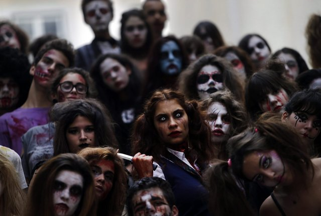 A group of youngsters dressed as ghouls and zombies for Halloween pose for a photograph as they parade in downtown Lisbon, Portugal, Friday, October 31, 2014. (Photo by Francisco Seco/AP Photo)