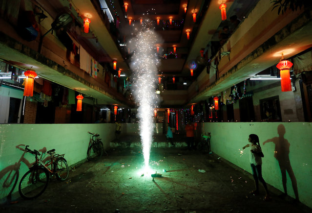 A girl plays with firecrackers while celebrating the Hindu festival of Diwali, the annual festival of lights in Mumbai, India, October 19, 2017. (Photo by Danish Siddiqui/Reuters)
