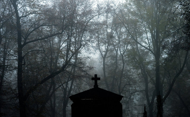 An grave at the foggy Olsany Cemetery during All Souls' Day in Prague, Czech Republic, 2 November 2014. All Saints' and All Souls' Day is a Christian festival mainly celebrated by Catholics to remember the dead. People visits the graves of loved ones and place candles and flowers. (Photo by Filip Singer/EPA)