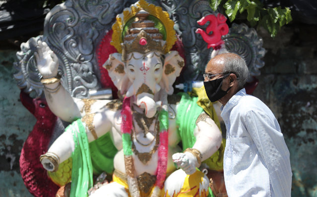 A man wearing a face masks walks past an idol of elephant-headed Hindu god Ganesha during reimposed weekend lockdown to prevent the spread of the coronavirus in Jammu, India Saturday, August 22, 2020. (Photo by Channi Anand/AP Photo)