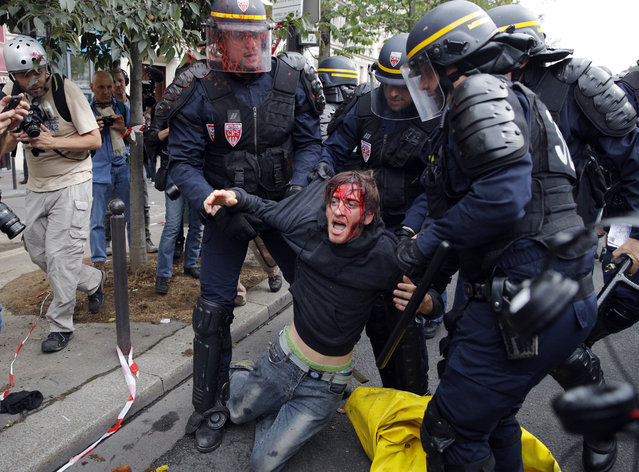 A wounded demonstrator is being evacuated by riot police following scuffles between protesters and the police as part of a protest against a labor law, in Paris, France, Thursday, September 15, 2016. Police With strikes and protests, French unions are staging a last-ditch bid to dismantle a labor law that weakens their powers and worker protections. (Photo by Christophe Ena/AP Photo)