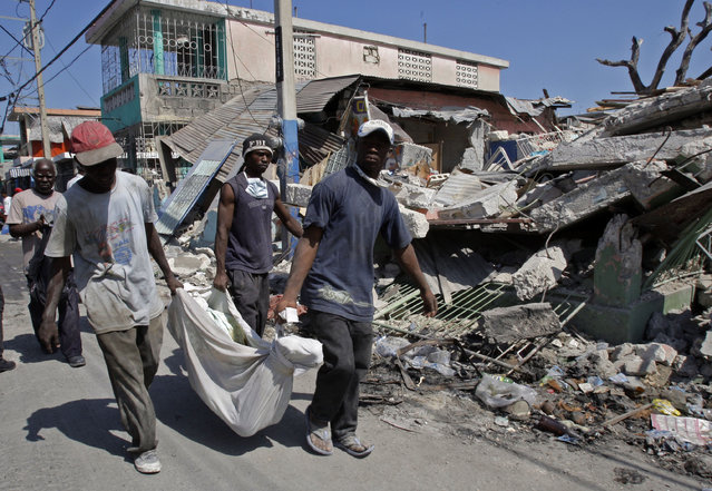 Men carry the body of 24-year-old Sergeline Joseph after they were paid by her father Thomas Silvain, rear left, more than US$200 to retrieve her from the rubble of their collapsed house instead of waiting for demolition crews, in Port-au-Prince, Tuesday, February 2, 2010. (Photo by Andres Leighton/AP Photo)