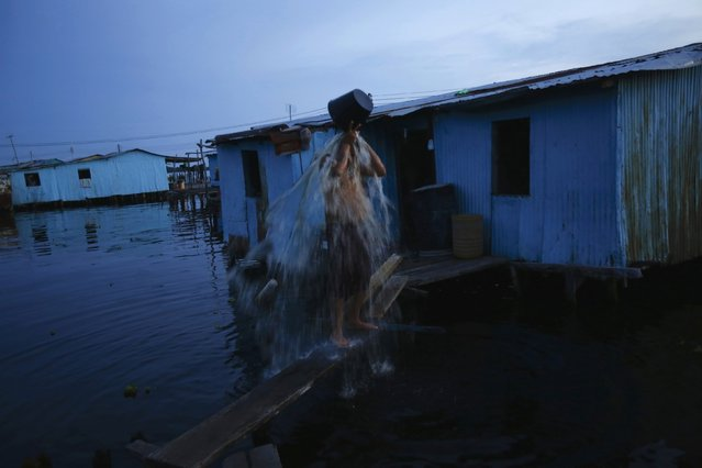 A fisherman washes outside his stilt house in the village of Ologa in the western state of Zulia October 22, 2014. (Photo by Jorge Silva/Reuters)