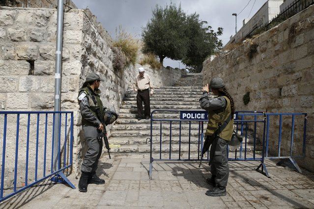 A Palestinian man walks down a flight of stairs as Israeli border police women stand guard at an entrance to Jerusalem's Old City October 9, 2015. (Photo by Baz Ratner/Reuters)
