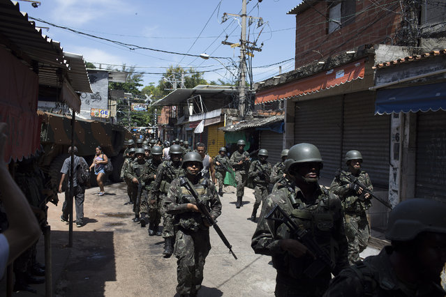 Soldiers take part in a surprise operation in Jacarezinho slum in Rio de Janeiro, Brazil, Thursday, January 18, 2018. (Photo by Leo Correa/AP Photo)