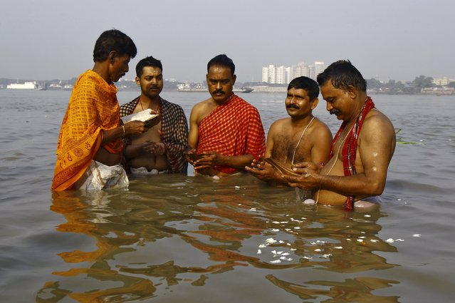 A Hindu priest (L) performs Tarpana, a religious ritual, as he helps the men to pray on the banks of the Ganges river on the holy day of Mahalaya in Kolkata, India, October 12, 2015. Hindus offer prayers with holy water after taking a dip in the river to honour the souls of their departed ancestors during Mahalaya, which is also called Pitru Paksha. (Photo by Rupak De Chowdhuri/Reuters)