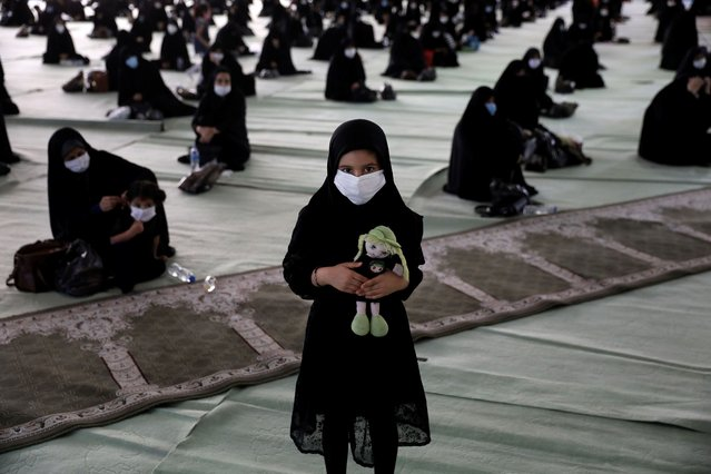 A girl wearing a protective face mask to help prevent spread of the coronavirus holds her doll as she attends a mourning ceremony to commemorate the 7th century death of Prophet Muhammad's grandson Hussein, one of Shiite Islam's most beloved saints, who was killed in a battle in Karbala in present-day Iraq, at the Tehran University Musalla, Iran, Saturday, August 29, 2020. The organizers arranged for the processions to take place with physical distancing, made face masks mandatory, checked mourners' body temperature and had them use hand sanitizers in an attempt to keep the gathering safe. Every year, millions of believers and followers of Shiite Islam flock to mosques for the ritual but this year the virus pandemic has scaled it down. (Photo by Vahid Salemi/AP Photo)