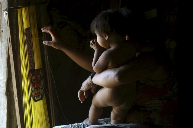 An indigenous woman from the Kamayura tribe works on a handicraft as she holds her child inside her house in their village at Xingu national park in Mato Grosso, Brazil, October 2, 2015. (Photo by Paulo Whitaker/Reuters)