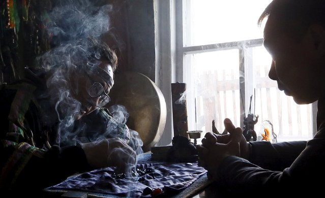 Vyacheslav Arapchor (L), a shaman representing the so-called Dungur society, conducts a session to clarify and predict the destiny of a customer, a local resident, at his residence in the town of Kyzyl, the administrative centre of Tuva region, Southern Siberia, Russia, October 7, 2015. (Photo by Ilya Naymushin/Reuters)