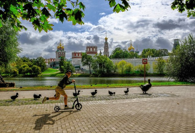 A boy rides a scooter near the Novodevichy Convent in central Moscow on September 14, 2020. (Photo by Yuri Kadobnov/AFP Photo)