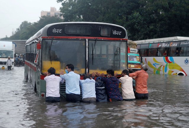 People push a bus through a waterlogged road after heavy rainfall in Mumbai, India, September 23, 2020. (Photo by Francis Mascarenhas/Reuters)