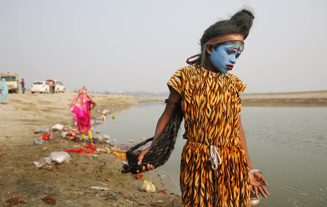 A young Indian boy dressed as Hindu God Shiva walks the banks of the River Ganges looking for alms from devotees on the first day of the nine-day Navratri festival, in Allahabad, India,Tuesday, October 13, 2015.  Navaratri lasts for nine days, with three days each devoted to the worship of  the goddess of valor Durga, the goddess of wealth Lakshmi, and the goddess of knowledge Saraswati. (Photo by Rajesh Kumar Singh/AP Photo)