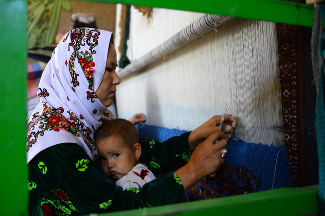 A woman holds her child as she works in a carpet factory in Guzara district of Herat province on September 28, 2020. (Photo by Hoshang Hashimi/AFP Photo)