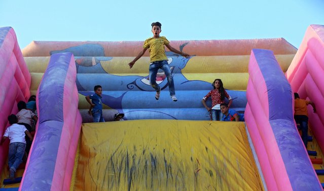Jordanian kids playing on a slider during the Eid celebration in Amman, Jordan, 12 September 2016. Eid al-Adha is the holiest of the two Muslims holidays celebrated each year, it marks the yearly Muslim pilgrimage (Hajj) to visit Mecca, the holiest place in Islam. Muslims slaughter a sacrificial animal and split the meat into three parts, one for the family, one for friends and relatives, and one for the poor and needy. (Photo by Jamal Nasrallah/EPA)