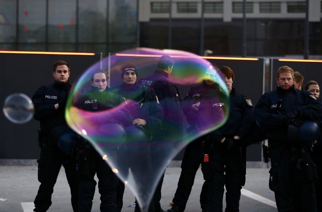German riot police officers are pictured through a soap bubble after a demonstration of Blockupy protesters against the opening of the new European Central Bank (ECB) headquarters in Frankfurt, November 22, 2014. (Photo by Kai Pfaffenbach/Reuters)