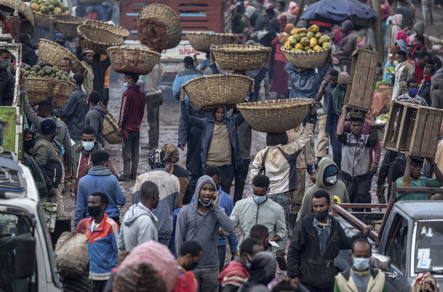 """Traders carry baskets of vegetables through muddy pathways in Atkilt Tera, the largest open-air vegetable market, in the capital Addis Ababa, Ethiopia Thursday, September 10, 2020. Ethiopians are stocking up on food on new year's eve of the Ethiopian calendar ahead of the holiday of """"Enkutatash"""", the first day of the new year that is traditionally associated with the return of the Queen of Sheba to Ethiopia some 3,000 years ago. (Photo by Mulugeta Ayene/AP Photo)"""