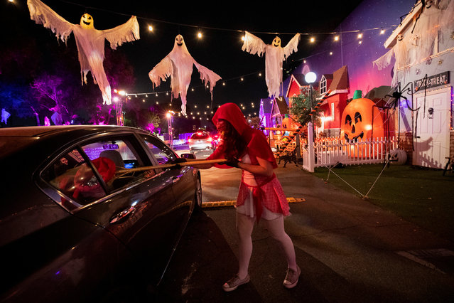"""A costumed actor hands out candy during the """"HAUNTOWEEN LA"""" Halloween drive through experience in Woodland Hills, California, U.S., October 8, 2020. (Photo by Mario Anzuoni/Reuters)"""