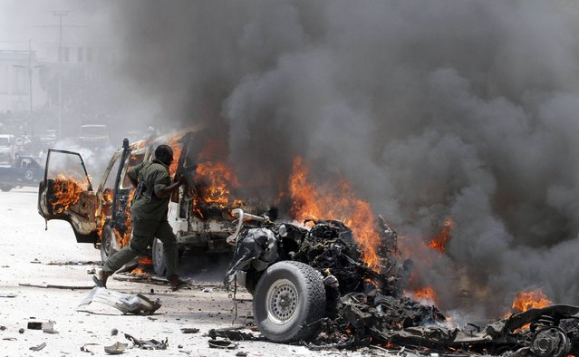 A policeman runs through burning vehicles at the scene of an explosion near the presidential palace in Somalia's capital Mogadishu, March 18, 2013. A car bomb exploded near the presidential palace in the Somali capital Mogadishu on Monday, killing at least 10 people in a blast that appeared to target senior government officials, police said. (Photo by Feisal Omar/Reuters)