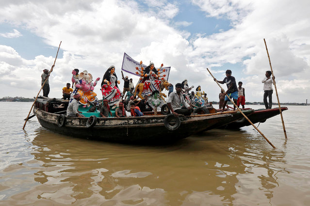 Idols of Hindu goddess Durga are transported on boats through the waters of river Ganga to pandals, or temporary platforms, ahead of the Durga Puja festival in Kolkata, India, September 29, 2016. (Photo by Rupak De Chowdhuri/Reuters)