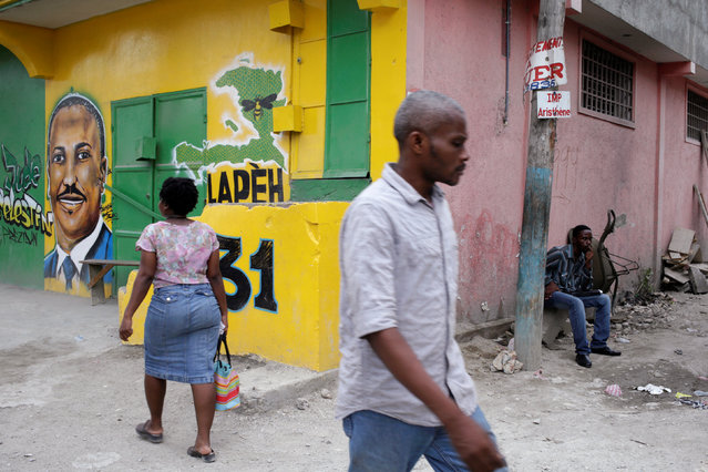 People walk next to a painting of presidential candidate Jude Celestin in a street of Port-au-Prince, Haiti, September 28, 2016. (Photo by Andres Martinez Casares/Reuters)