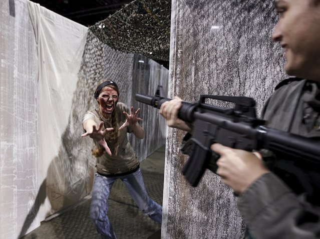 """Dakota Bourdon rounds the corner to be greeted by a zombie at the Apocalypse Zombie Experience at The Walker Stalker Convention in Atlanta, Georgia, October 30, 2015. The convention also showcases advanced special effects and cosplay techniques along with the stars of """"The Walking Dead"""" television show and various other type shows. (Photo by Tami Chappell/Reuters)"""
